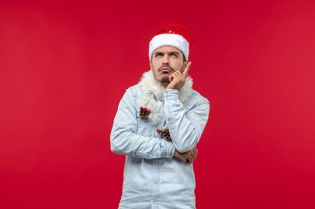 Vista frontal de um jovem com expressão pensativa na parede vermelha