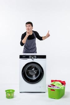 Vista frontal de um jovem com máquina de lavar e roupas sujas na parede branca