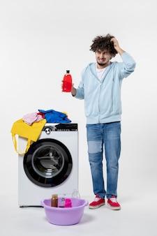 Vista frontal de um jovem com máquina de lavar segurando pó líquido na parede branca
