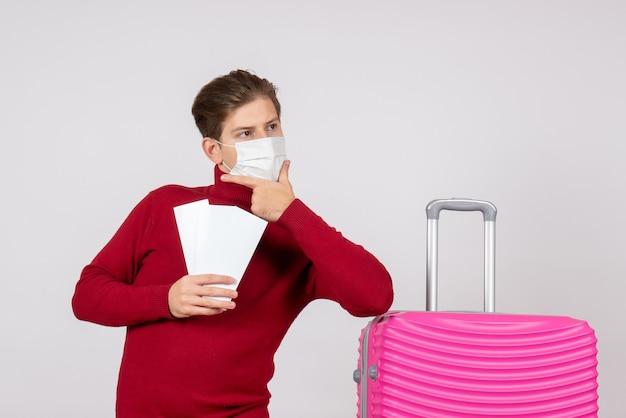 Vista frontal de um jovem com máscara segurando passagens de avião na parede branca