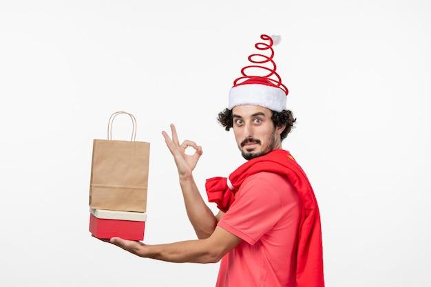 Vista frontal de um jovem com presentes de feriado na parede branca