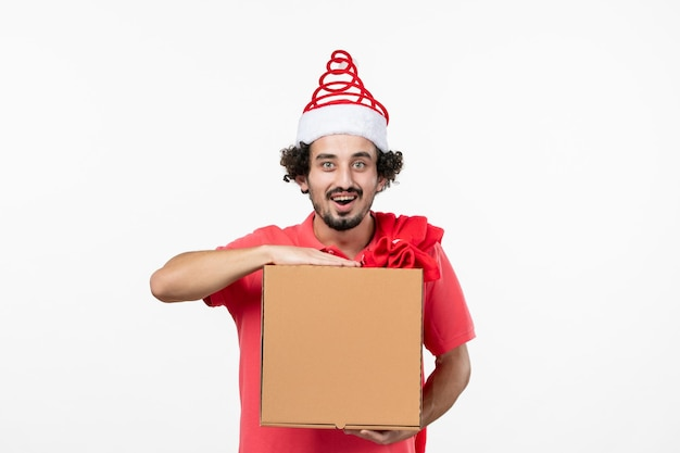 Vista frontal de um jovem com uma caixa de comida de entrega na parede branca