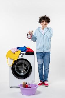 Vista frontal de um jovem com uma lavadora segurando relógios na parede branca