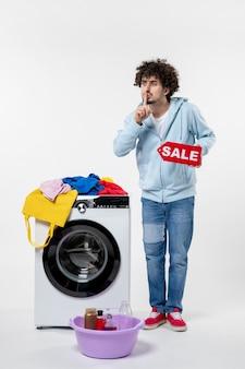 Vista frontal de um jovem com uma lavadora segurando uma bandeira vermelha de venda na parede branca