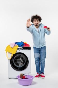 Vista frontal de um jovem com uma máquina de lavar segurando um cartão vermelho e pedindo para parar na parede branca
