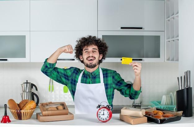 Vista frontal de um jovem confiante e feliz em pé atrás da mesa, vários doces e mostrando o cartão do banco na cozinha branca