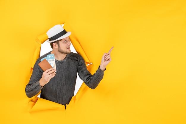 Vista frontal de um jovem confuso com um chapéu, segurando um passaporte estrangeiro com passagem e apontando para cima em uma parede amarela rasgada