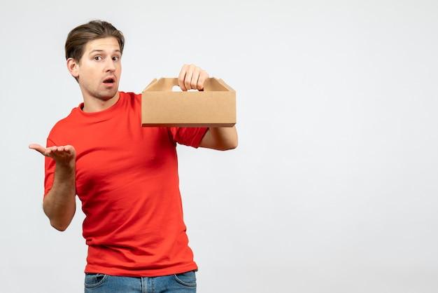 Vista frontal de um jovem confuso com uma blusa vermelha segurando uma caixa no fundo branco