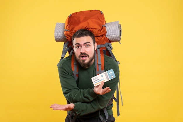 Vista frontal de um jovem confuso viajando com uma mochila e mostrando a passagem em fundo amarelo
