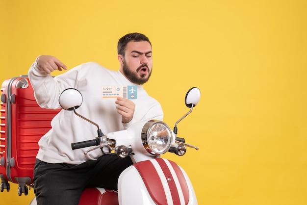 Vista frontal de um jovem confuso viajando sentado em uma motocicleta com uma mala segurando o bilhete em fundo amarelo isolado