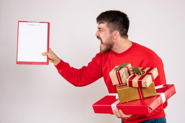 Vista frontal de um jovem de camisa vermelha segurando presentes de natal, discutindo na parede branca