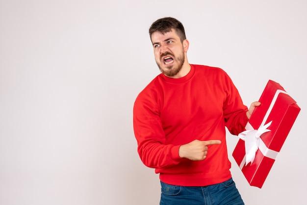 Vista frontal de um jovem de camisa vermelha segurando um presente de natal e discutindo com alguém na parede branca
