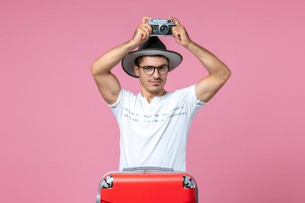 Vista frontal de um jovem de férias com uma bolsa segurando a câmera, tirando fotos na parede rosa