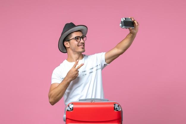 Vista frontal de um jovem de férias com uma bolsa vermelha tirando fotos na parede rosa