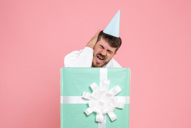 Vista frontal de um jovem de pé dentro da caixa de presente e com dor de cabeça na parede rosa