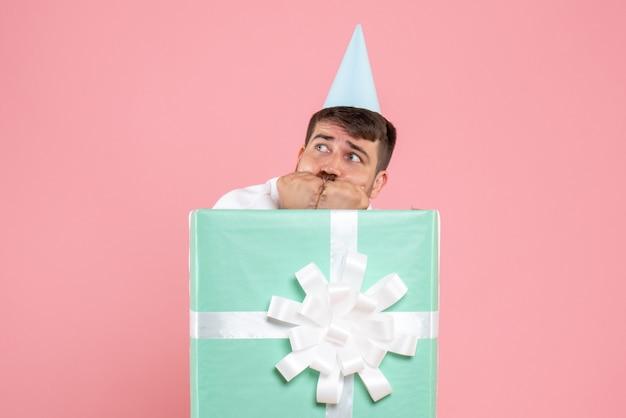 Vista frontal de um jovem de pé dentro da caixa de presente em uma parede rosa Foto gratuita