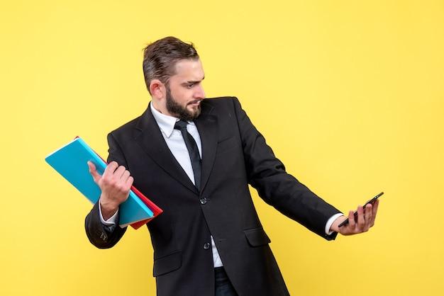 Vista frontal de um jovem de terno preto segurando pastas e olhando suspeito para um telefone amarelo
