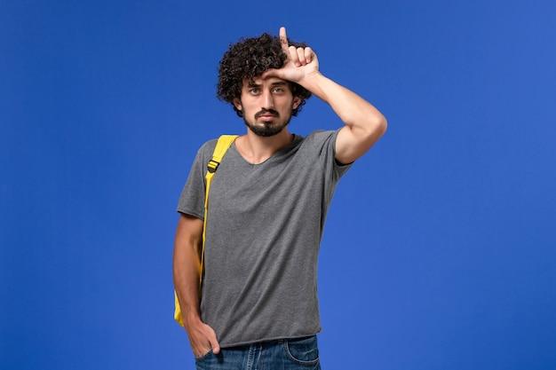 Vista frontal de um jovem do sexo masculino com uma camiseta cinza e uma mochila amarela, apenas posando na parede azul-clara