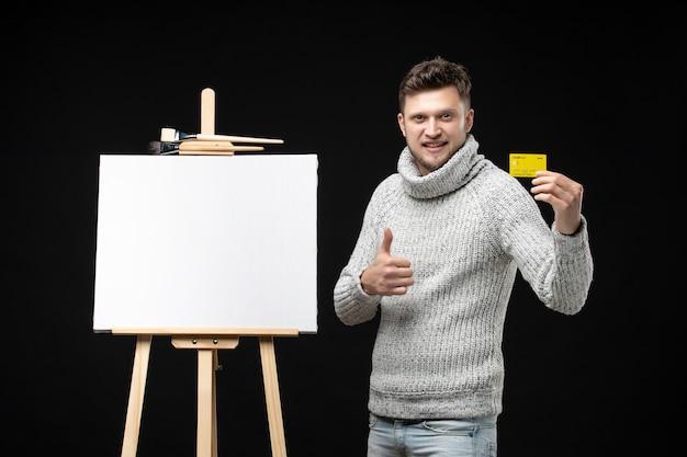 Vista frontal de um jovem e talentoso artista masculino segurando um cartão do banco, fazendo um gesto de ok no preto