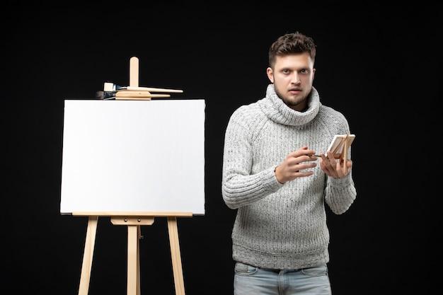 Vista frontal de um jovem e talentoso artista masculino segurando um mini-livro com pincel, posando para a câmera no preto
