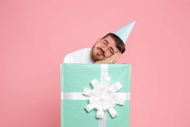 Vista frontal de um jovem em pé dentro da caixa de presentes e dormindo na parede rosa