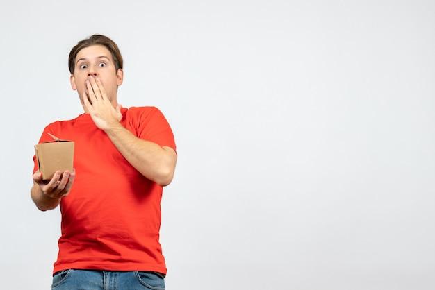 Vista frontal de um jovem emocional chocado com uma blusa vermelha segurando uma pequena caixa no fundo branco