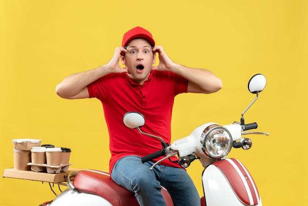 Vista frontal de um jovem emocional louco, usando uma blusa vermelha e um chapéu, entregando pedidos em fundo amarelo