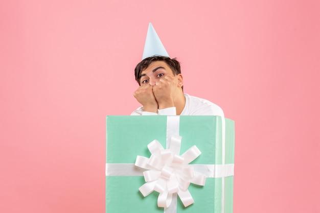 Vista frontal de um jovem escondido dentro de um presente nervoso na parede rosa
