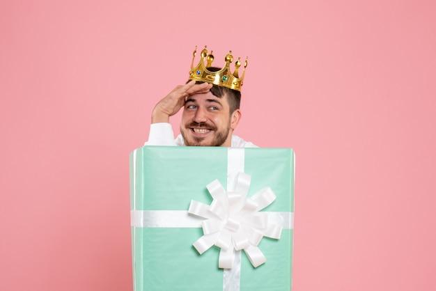 Vista frontal de um jovem escondido dentro de uma caixa de presente com uma coroa na parede rosa