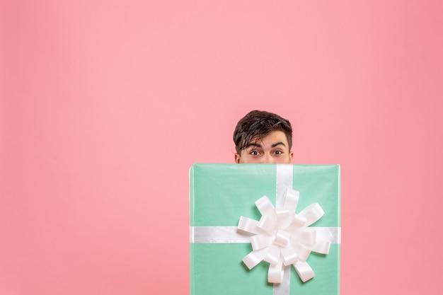 Vista frontal de um jovem escondido dentro do presente na parede rosa Foto gratuita