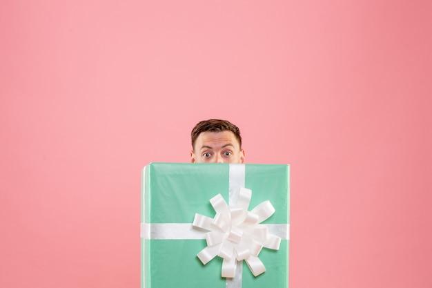 Vista frontal de um jovem escondido dentro do presente na parede rosa