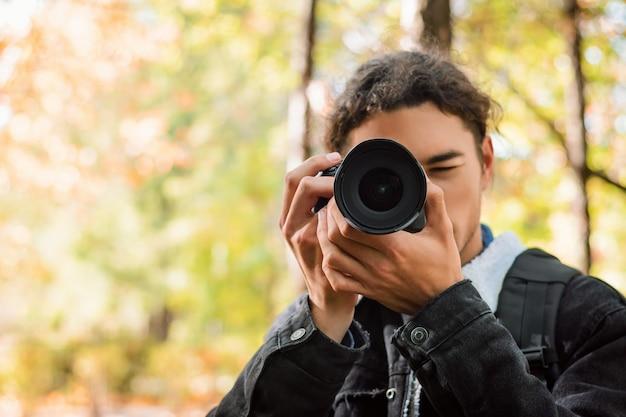 Vista frontal de um jovem estudante tirando fotos para seu projeto sobre o assunto natureza e história do cinema