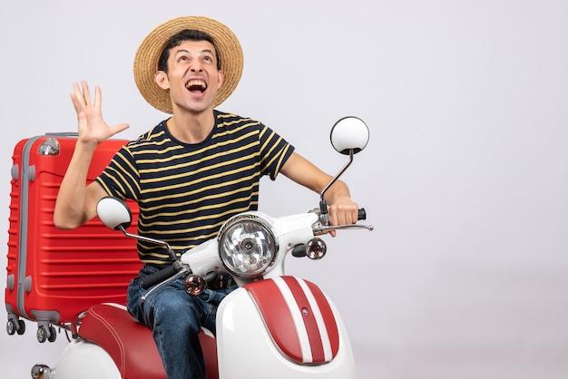 Vista frontal de um jovem exultante com chapéu de palha na motocicleta, de pé no fundo branco