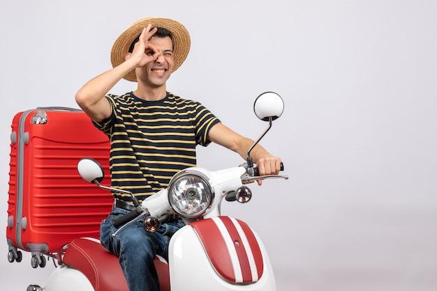 Vista frontal de um jovem feliz com chapéu de palha na motocicleta, colocando a placa de ok na frente do olho