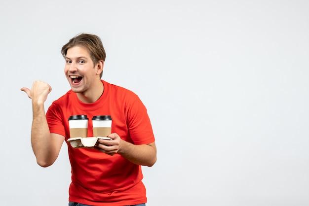 Vista frontal de um jovem feliz com uma blusa vermelha segurando uma pequena caixa e apontando para trás no fundo branco