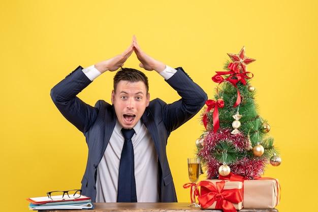 Vista frontal de um jovem feliz fazendo telhado da casa com as mãos, sentado à mesa perto da árvore de natal e presentes em amarelo