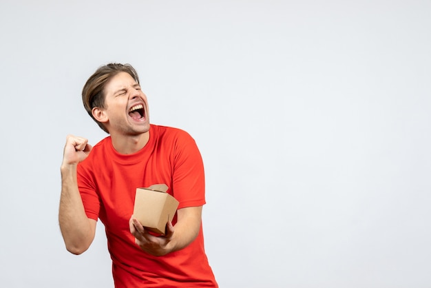 Vista frontal de um jovem feliz sorridente com uma blusa vermelha segurando uma pequena caixa no fundo branco