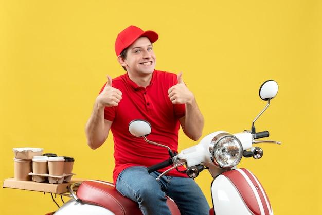 Vista frontal de um jovem feliz sorridente, vestindo uma blusa vermelha e um chapéu, entregando pedidos, fazendo um gesto de ok no fundo amarelo