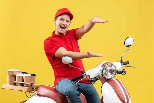 Vista frontal de um jovem feliz vestindo blusa vermelha e chapéu, entregando pedidos e fazendo algo exato sobre fundo amarelo