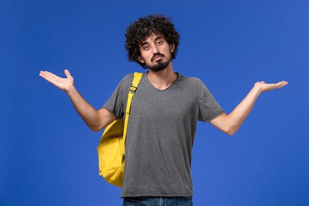 Vista frontal de um jovem homem com camiseta cinza e mochila amarela na parede azul