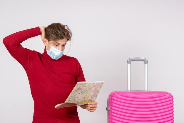 Vista frontal de um jovem homem com máscara, segurando e explorando o mapa na parede branca