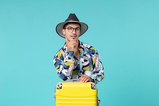 Vista frontal de um jovem homem com sua bolsa amarela se preparando para uma viagem pensando na parede azul