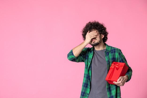 Vista frontal de um jovem homem com um pacote vermelho na parede rosa claro
