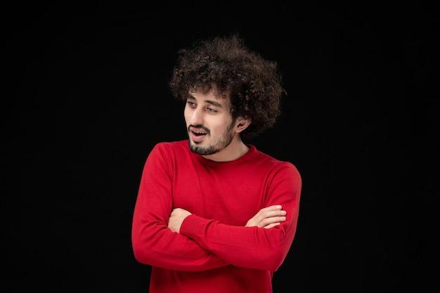 Vista frontal de um jovem homem com um suéter vermelho na parede preta