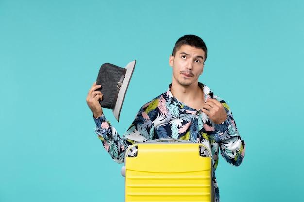 Vista frontal de um jovem homem com uma bolsa amarela segurando seu chapéu e se preparando para uma viagem na parede azul
