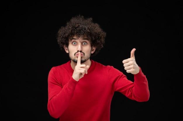 Vista frontal de um jovem homem de camisa vermelha pedindo para ficar em silêncio na parede preta