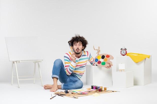 Vista frontal de um jovem homem desenhando pinturas na parede branca