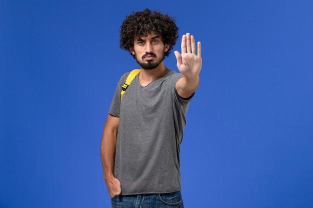 Vista frontal de um jovem homem em uma camiseta cinza usando uma mochila amarela mostrando o sinal de pare na parede azul-clara