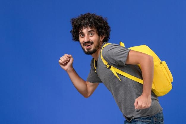 Vista frontal de um jovem homem em uma camiseta cinza usando uma mochila amarela, sorrindo e correndo na parede azul