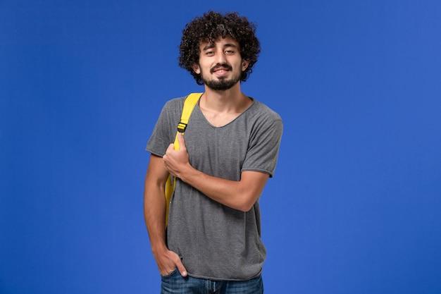 Vista frontal de um jovem homem em uma camiseta cinza usando uma mochila amarela, sorrindo levemente na parede azul